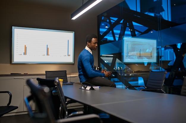 Zmęczony menedżer pozuje przy filiżance kawy, nocny styl życia w biurze. mężczyzna przy stole, ciemne wnętrze centrum biznesowego, nowoczesne miejsce pracy
