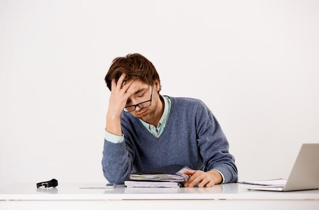 Zmęczony męski pracownik biurowy, wzdychający niespokojnie, pracujący do późna, mają terminy, studiuje raporty i dokumenty jak siedzieć przy stole z laptopem, twarz jest zakłopotany