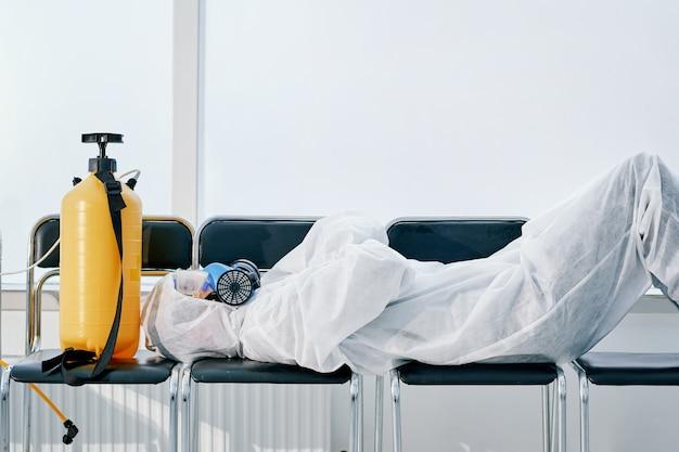 Zmęczony męski środek odkażający śpi na krzesłach w holu biura. walczyć z koronowirusem.
