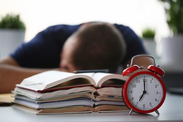 Zmęczony męski uczeń przy miejscem pracy w pokoju