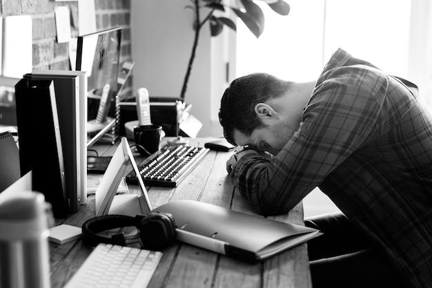 Zmęczony mężczyzna drzemiący na biurku