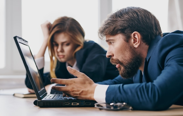Zmęczony mężczyzna i kobieta w pracy kolegów w pracy specjalistów laptopa