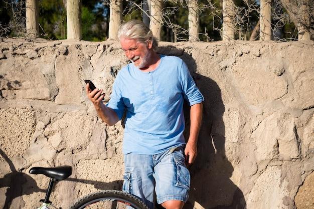 Zmęczony mężczyzna korzystający z telefonu lub komórki na świeżym powietrzu i uśmiechający się po pociągu na rowerze - piękny dzień i wakacje na rowerek