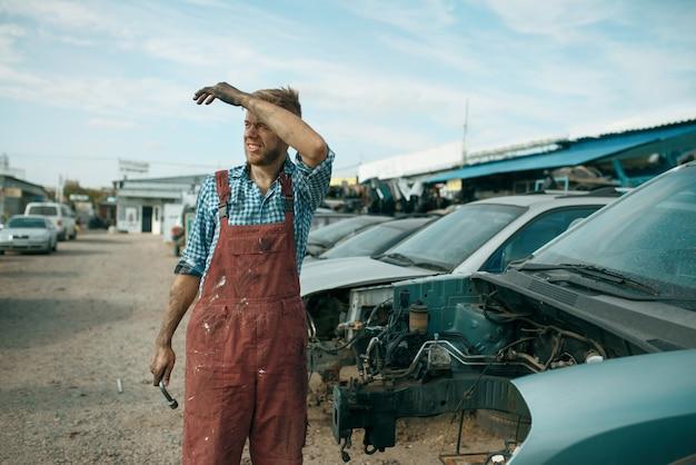 Zmęczony mężczyzna mechanik z kluczem na złomowisku samochodów.
