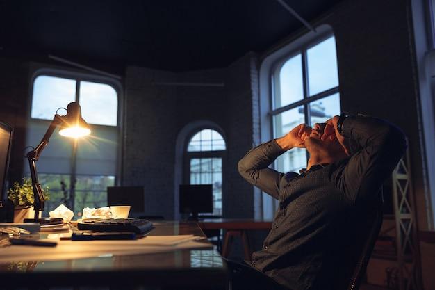 Zmęczony. mężczyzna pracujący samotnie w biurze podczas kwarantanny koronawirusa lub covid-19, przebywający do późna w nocy. młody biznesmen, kierownik wykonujący zadania z smartphone, laptop, tablet w pustym obszarze roboczym.
