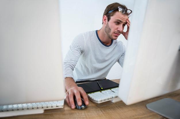 Zmęczony mężczyzna pracuje na komputerze w jaskrawym biurze