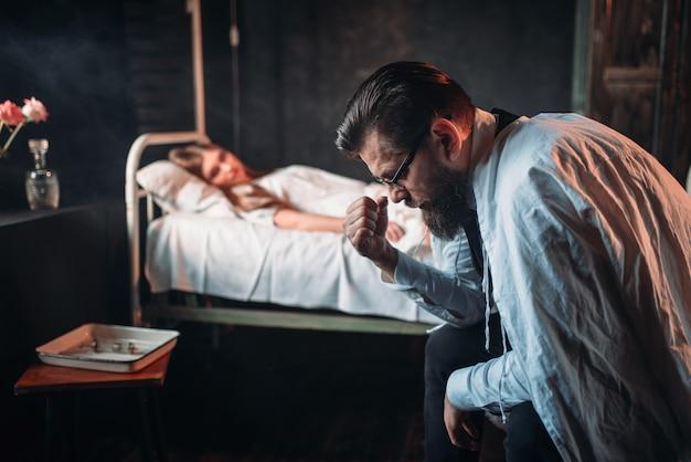Zmęczony mężczyzna przeciwko chorej kobiecie w szpitalnym łóżku