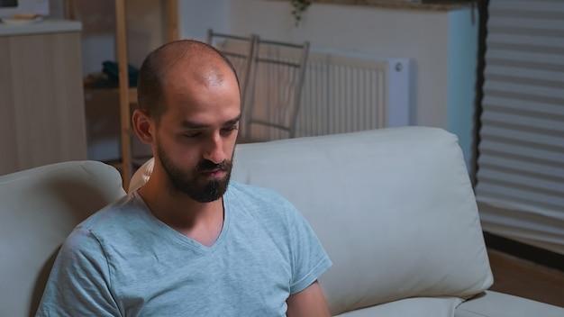 Zmęczony mężczyzna siedzący przed telewizorem, piszący informacje o stylu życia