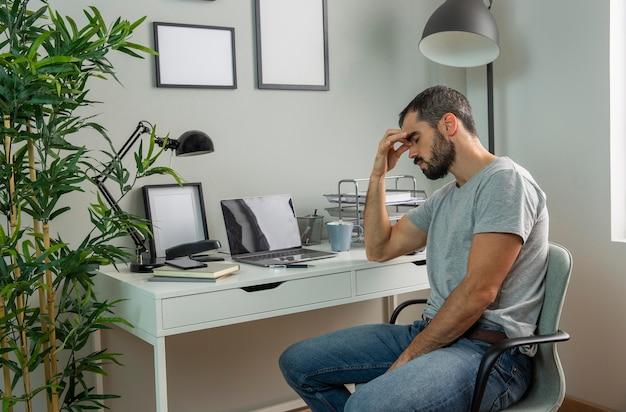 Zmęczony mężczyzna siedzi przy biurku w domu