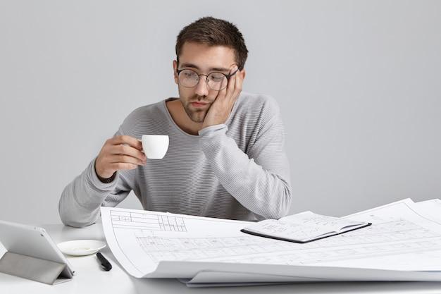 Zmęczony mężczyzna wygląda na zmęczonego po pracy przez cały wieczór na rysunkach, patrzy na filiżankę espresso lub cappucino