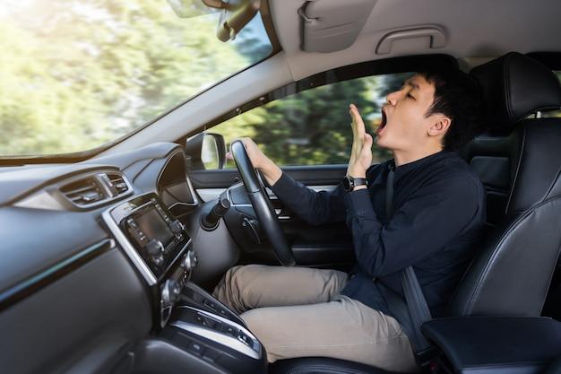 Zmęczony mężczyzna ziewa i śpi podczas jazdy samochodem