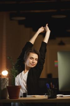 Zmęczony młoda kobieta projektanta obsiadanie w biurze