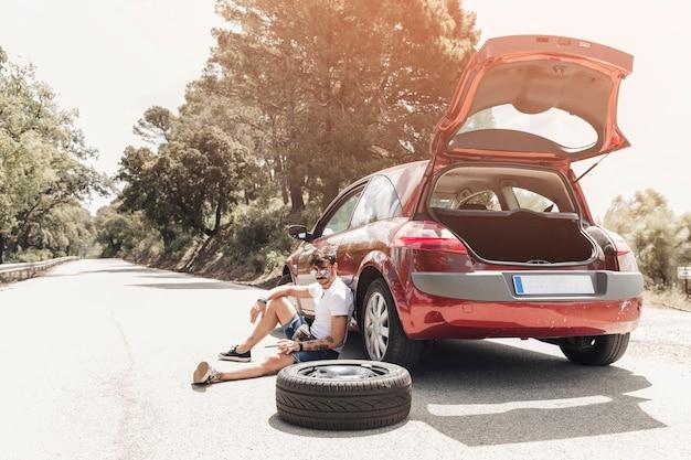 Zmęczony młodego człowieka obsiadanie blisko łamanego puszka samochodu na drodze