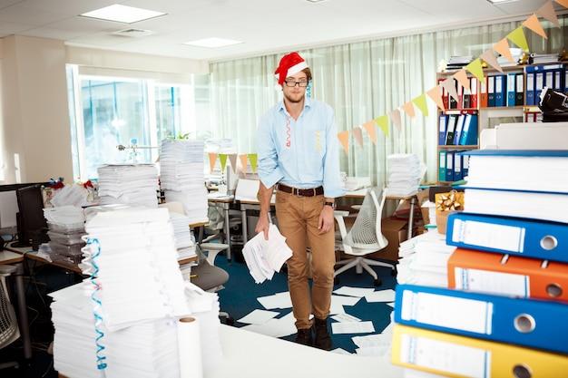 Zmęczony młody biznesmen pracuje w biurze wśród papierów na święto bożęgo narodzenia.