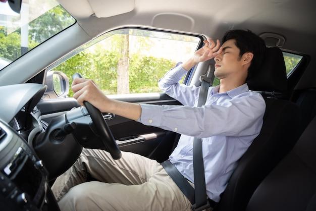 Zmęczony młody biznesmen z azji śpi w samochodzie
