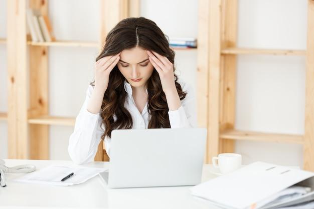 Zmęczony młody bizneswoman cierpi na długi czas siedząc przy biurku w biurze.