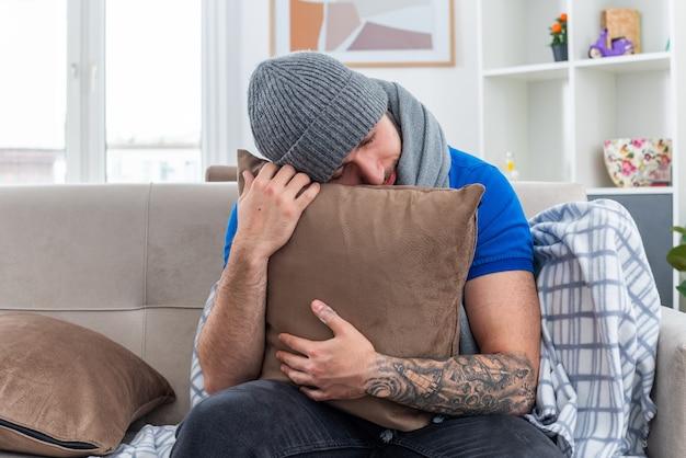 Zmęczony młody chory człowiek ubrany w szalik i czapkę zimową, siedzący na kanapie w salonie, przytulając poduszkę, opierając głowę z zamkniętymi oczami
