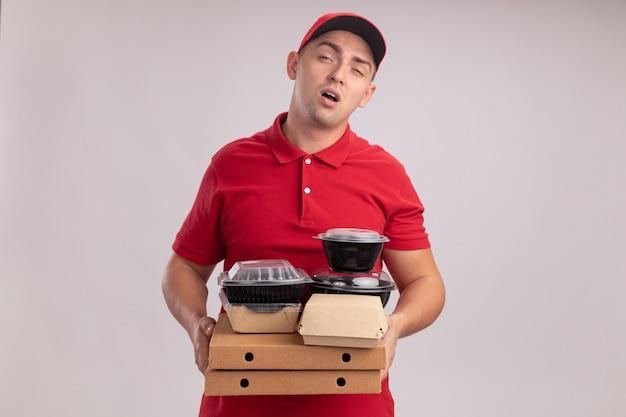 Zmęczony młody człowiek dostawy ubrany w mundur z czapką, trzymając pojemniki na żywność na pudełkach po pizzy na białym tle na białej ścianie