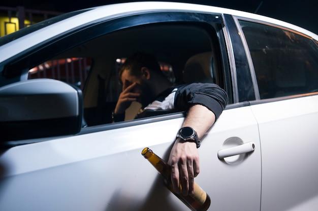 Zmęczony młody człowiek jazdy samochodem. śpi w swoim samochodzie, wyczerpany.
