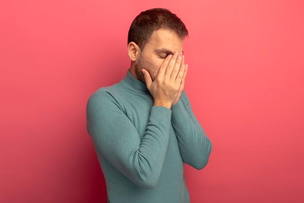 Zmęczony młody człowiek kaukaski kładąc ręce na twarzy z zamkniętymi oczami na białym tle na szkarłatnej ścianie z miejsca na kopię