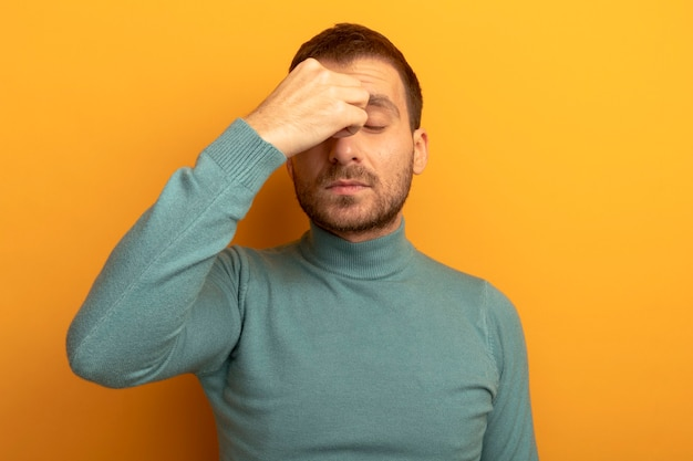 Zmęczony młody człowiek kaukaski, kładąc rękę na nosie z zamkniętymi oczami na białym tle na pomarańczowej ścianie z miejsca na kopię