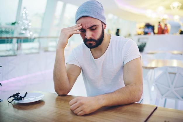 Zmęczony młody człowiek ma ból głowy. usiądź w kawiarni i trzymaj rękę na głowie. hipster złapał przeziębienie lub ból głowy. usiądź w restauracji lub kawiarni odern.