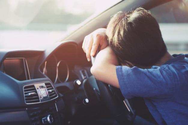 Zmęczony młody człowiek podczas prowadzenia samochodu. śpi w swoim samochodzie, wyczerpany.