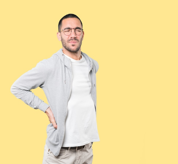 Zmęczony młody człowiek pozuje przeciw tłu