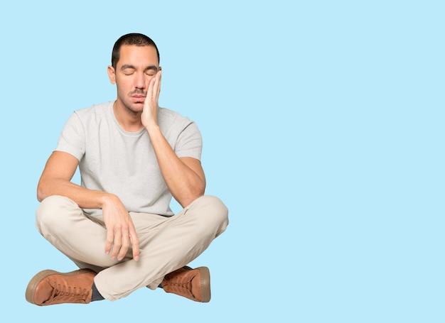 Zmęczony młody człowiek robi gest znudzenia