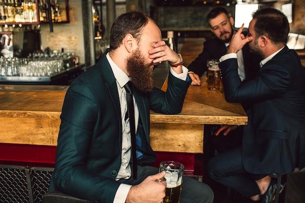 Zmęczony młody człowiek siedzieć i przykryć twarz ręką. dwóch innych mężczyzn siedzi i rozmawia. są w barze.