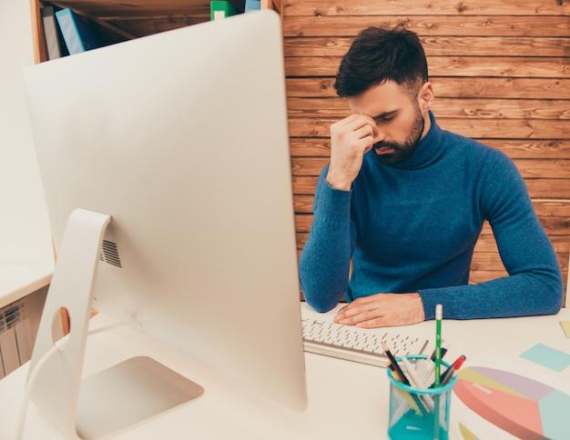 Zmęczony młody człowiek smutny myśli o problemach w pracy