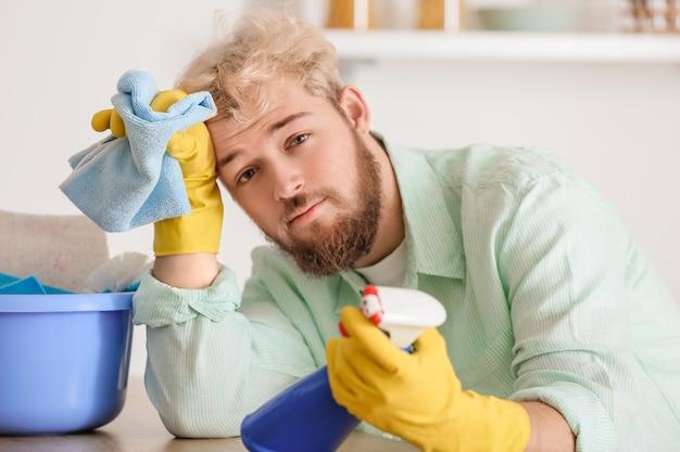 Zmęczony młody człowiek ze środkami czystości w kuchni