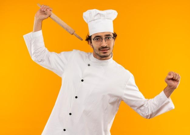 Zmęczony młody kucharz mężczyzna ubrany w mundur szefa kuchni i okulary trzymając wałek do ciasta i robi rozciąganie na białym tle na żółtej ścianie