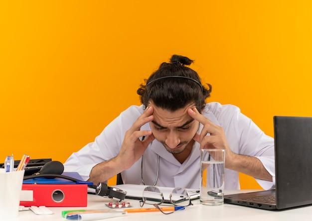 Zmęczony młody lekarz mężczyzna w okularach medycznych, ubrany w szatę medyczną ze stetoskopem, siedzący przy biurku