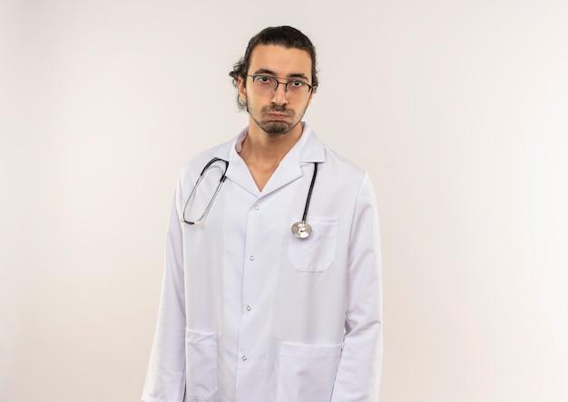 Zmęczony młody lekarz mężczyzna z okularami optycznymi na sobie białą szatę ze stetoskopem na odizolowanej białej ścianie z miejsca na kopię