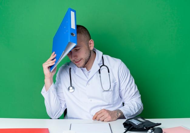 Zmęczony młody lekarz płci męskiej ubrany w szlafrok medyczny i stetoskop siedzi przy biurku z narzędziami do pracy, trzymając folder i dotykając nim głowy z zamkniętymi oczami na białym tle na zielonym tle