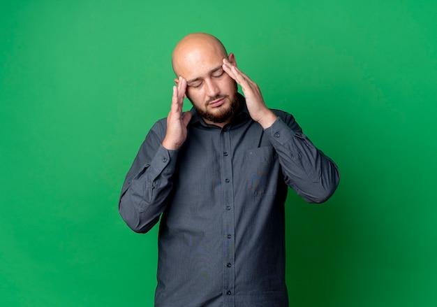 Zmęczony młody łysy mężczyzna call center kładzie ręce na skroniach z zamkniętymi oczami na białym tle na zielonej ścianie
