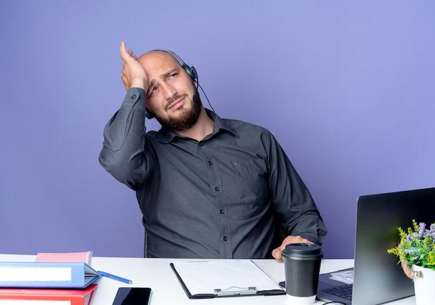 Zmęczony młody łysy mężczyzna call center sobie zestaw słuchawkowy siedzi przy biurku z narzędziami pracy, kładąc rękę na głowie i patrząc w górę na białym tle na fioletowej ścianie