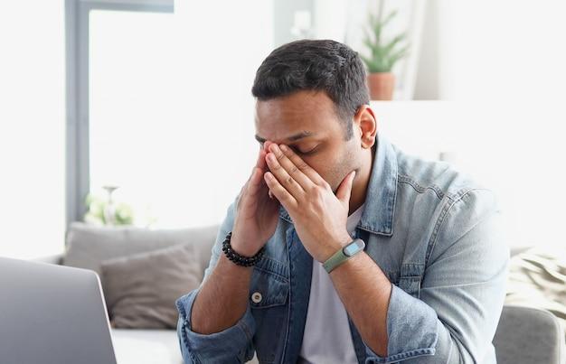 Zmęczony młody mężczyzna z indii odczuwa zmęczenie oczu od komputera siedzącego przy biurku w biurze, siedzący tryb życia, mężczyzna na skraju emocjonalnego stresu z powodu przepracowania w pracy