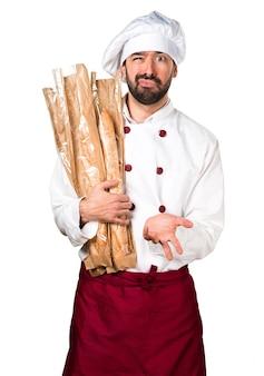 Zmęczony młody piekarz trzyma chleb