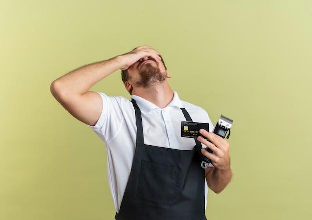 Zmęczony młody przystojny fryzjer, trzymając kartę kredytową i maszynki do strzyżenia włosów, kładąc rękę na oczy na białym tle na oliwkowej ścianie