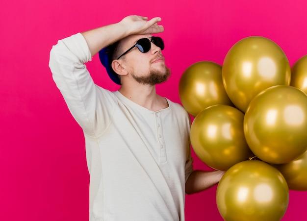 Zmęczony młody przystojny słowiański imprezowicz w kapeluszu imprezowym i okularach przeciwsłonecznych, trzymając balony, patrząc w górę, trzymając rękę na czole na białym tle na szkarłatnym tle