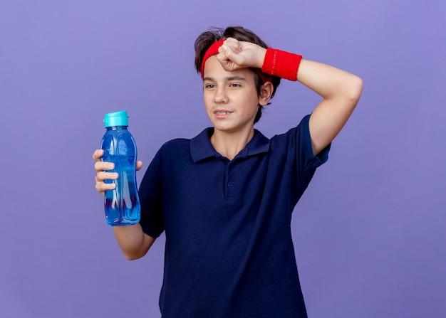 Zmęczony młody przystojny sportowy chłopak noszący opaskę i opaski na nadgarstki z aparatami ortodontycznymi patrząc na bok, trzymając butelkę wody, wycierając pot ręką odizolowaną na fioletowej ścianie