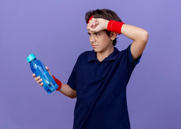 Zmęczony młody przystojny sportowy chłopiec noszący opaskę i opaski na nadgarstki z aparatami ortodontycznymi kładący dłoń na czole, trzymając i patrząc na butelkę wody na fioletowej ścianie