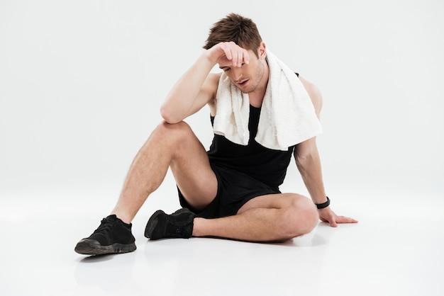Zmęczony młody sportowiec z ręcznikiem, siedząc na podłodze