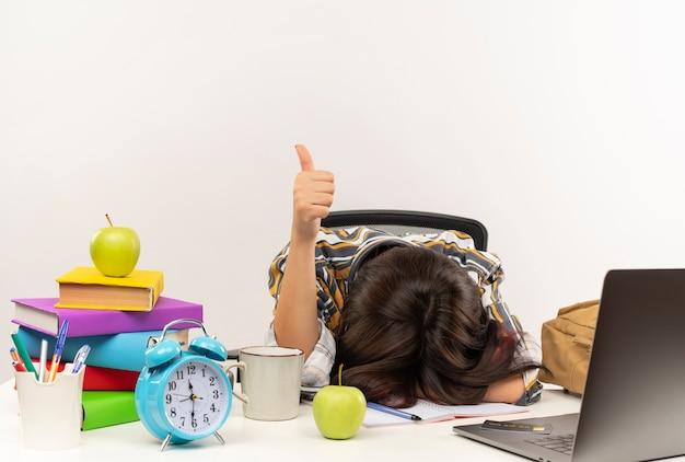 Zmęczony młody student dziewczyna w okularach siedzi przy biurku z narzędziami uniwersyteckimi i kładąc głowę na biurku i pokazując kciuk do góry na białym tle