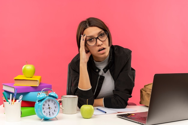 Zmęczony młody student dziewczyna w okularach siedzi przy biurku z narzędziami uniwersytetu, kładąc rękę na czole na białym tle na różowym tle