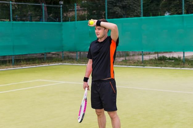 Zmęczony młody tenisista mężczyzna ubrany w sportową, trzymając piłkę tenisową i rakietę po meczu na korcie na świeżym powietrzu w lecie