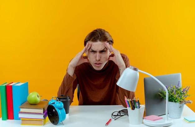 Zmęczony młody uczeń chłopiec siedzi przy biurku z narzędziami szkolnymi, kładąc ręce wokół oczu na białym tle na żółtej ścianie