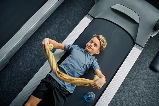 Zmęczony młodzieniec leżący na bieżni w siłowni, uruchomiona maszyna. chłopiec na treningu, opiece zdrowotnej i zdrowym stylu życia, uczeń na treningu